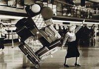 Senhora carregando carrinho com malas